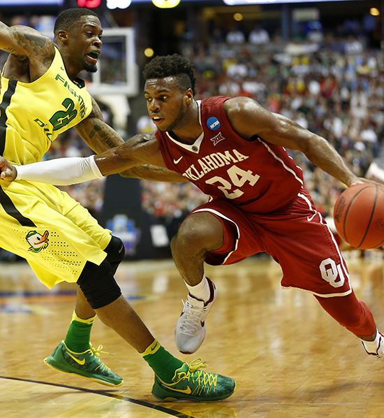 Oklahoma's Buddy Hield (right) drives to the basket against Oregon's Elgin Cook during the first half in the finals of the NCAA Tournament's West region at the Honda Center in Anaheim, Calif., on March 26. Oklahoma advanced, 80-68.