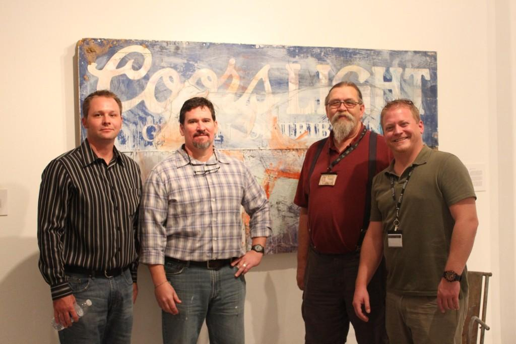 Left to right: Artist Chad Hines ad San Jac professors Todd Allison, MIchael Unger, and Daniel Longtin stand in front of one of the pieces from the exhibit.