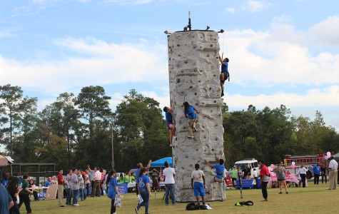 Potential North campus students scale the rock climbing wall at C.E. King Middle School while learning about educational options.