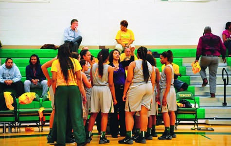Head Coach Brenita Jackson (facing) addresses the women's basketball team on the sidelines of North campus's Nichols Gymnasium.