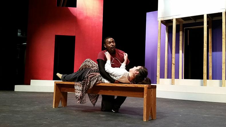 Chad Promise (left) embraces Dayan Perez (right) during rehearsals for spring musical.