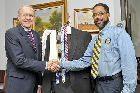 Men of Honor Director, Ronald Hopkins, accepts a clothing donation from attorney Daniel Snooks.