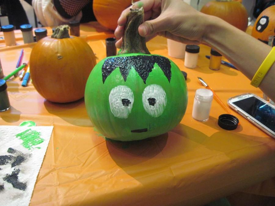 A student proudly holds a Frankenstein pumpkin from last year's painting event.
