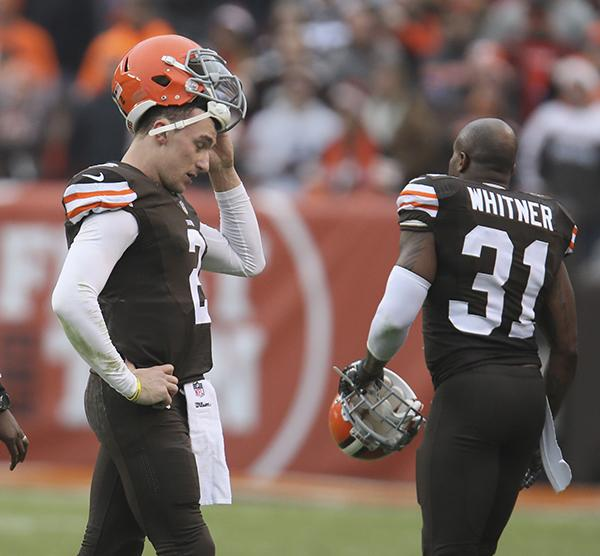 A defeated Manziel leaves the field after throwing an interception during a Dec. 14, 2014 game in Cleveland. He is back in the media spotlight amid allegations of domestic violence stemming from a Jan. 29 incident.
