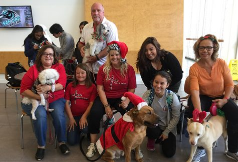 Rec Sports Director Butch Sutton (standing) holds his certified therapy dog, Mia, while posing with fellow Paws 4 Grace members and their service animals during a visit to Central Campus on Dec. 3, 2017.
